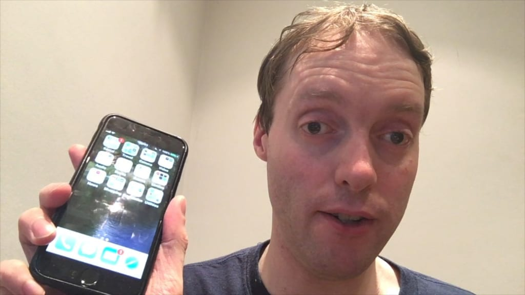 Glen, visually impaired blogger and Youtuber based in London, holding his phone up to show the camera.