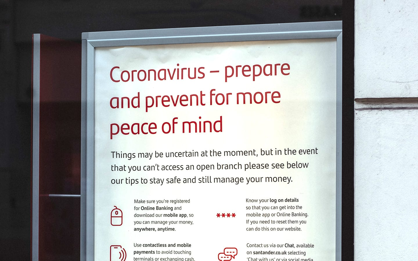 """Poster reads """"Coronavirus, prepare and prevent for more peace of mind."""" Sign outside bank giving Coronavirus information about online banking alternatives."""